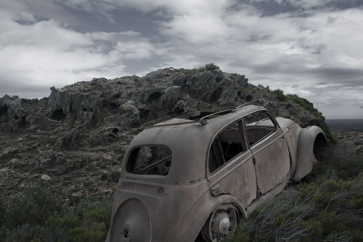 Broken mirror of humanity. Abandoned old car in surreal landscape